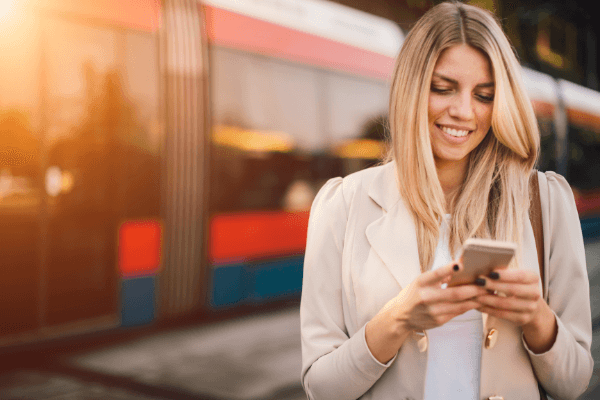 Smiling lady with mobile phone near a train